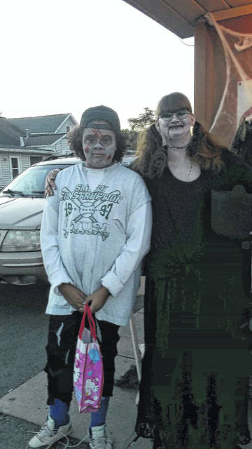 This ghoul from Thompson's Depot passed candy out Thursday evening during Beggar's Night in the City of Washington Court House. She is pictured with Onesti Evans, a zombie softball player.
