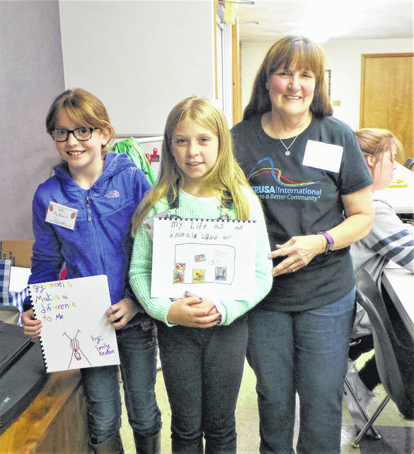 """Two young girls show off their newly-created books, based around the theme of """"X Makes a Difference to Me."""" Emily (on left) has described her love of gymnastics, and Bailey (in center) has written about being an animal lover. Altrusan Debra Grover (on right), who has just bound the books, headed the Washington C.H. Altrusa Club's service project along with co-chairs Elaine Crutcher and Anne Quinn. Other members of the club supplied refreshments, stuffed treat bags and acted as """"editors"""" during the Saturday afternoon workshop."""