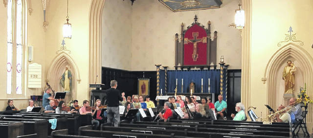 "Craig Jaynes, music director of the ""Concerts in a Country Church"" series, which is in its fifth season at St. Colman Church in Washington Court House, is shown here rehearsing the chorus and orchestra for a one-time performance of the ""Requiem"" by Wolfgang Amadeus Mozart. The concert will be held this Sunday at 3 p.m. with admission for $20."