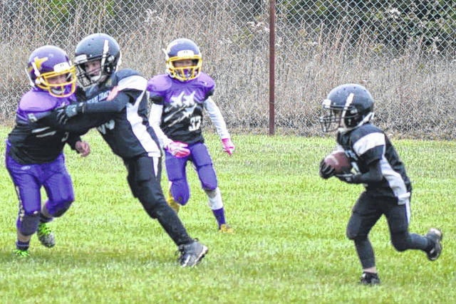 Evan Parsley at right, runs around the end for a large gain with Aiden White (53) providing key blocking as the 3rd grade White defeats Vandalia Purple 13-0, Saturday, Oct. 28, 2017.