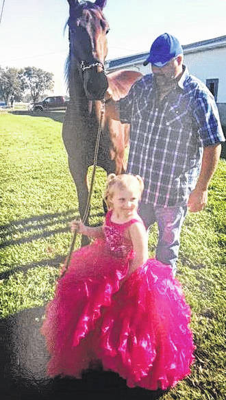 Horseman Joey George (at right) is pictured with Jasmine Wilkins who stopped at the Fayette County Fairgrounds recently to get a photo with a horse. She is pictured with the horse, Butter Bean, who is owned by Neil Glispie.