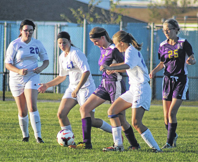 Washington Lady Blue Lion players (l-r) Dawn Johnson (20), Shawna Conger (21) and Savanna Davis surround a McClain player with the ball during a Frontier Athletic Conference match at Washington High School Tuesday, Oct. 3, 2017.