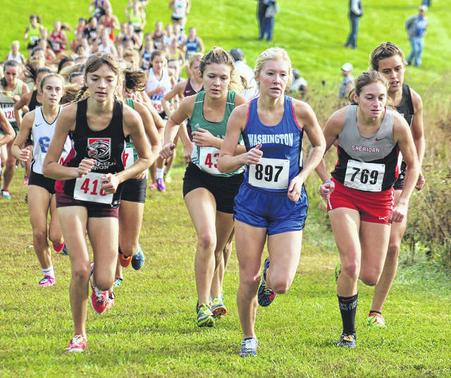 Washington's Maddy Garrison (wearing No. 897) runs at the front of the field going up a hill at Rio Grande in the District cross country meet Saturday, Oct. 21, 2017. Garrison placed sixth out of 122 runners to qualify to this Saturday's Regional meet at Pickerington North High School.