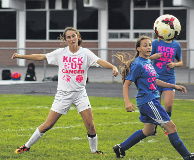 Miami Trace's Reagan Barton (left) watches the flight of her shot during a Frontier Athletic Conference match against Washington Thursday, Oct. 5, 2017. This shot hit the post and caromed in for a goal. Pictured for Washington is Zoee Clay.