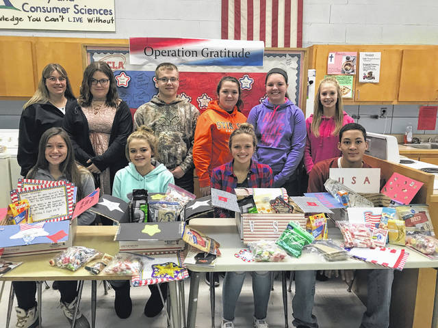"In honor of Veterans Day, Miami Trace/Great Oaks Family, Career, and Community Leaders of America (FCCLA) created care packages for active duty military serving overseas. In-class FCCLA members donated items and wrote a hundred letters of appreciation to service members. ""Many students included scripture, quotes or funny jokes in their words of encouragement,"" said instructor Elizabeth Arledge. Pictured from left to right in the back row: Mrs. Speakman, Emily Peloquin, Ryan Arledge, Haley Davis, Bethany Weidman, Shalyn Landrum. Front row from right to left: Hailee Schirm, Tabby Landrum, Kaylie Lott, and Todd Brown."