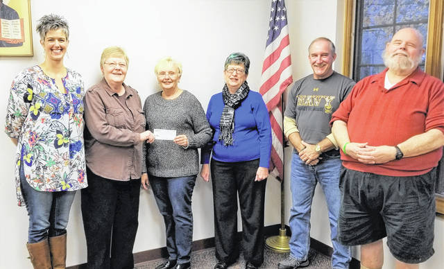 """Mary Jo Wall (second from left) accepts a check from Julia Hidy of the proceeds from the 2017 """"Come Grow With Us"""" project. This project is sponsored by St. Andrew's Episcopal Church and Good Shepherd Lutheran Church and will help St. Vincent de Paul at St. Colman of Cloyne Catholic Church. Pictured with Wall and Hidy are Shannon Jacobs, Claudia Coe, Doug Hosch and Charles Woodard."""