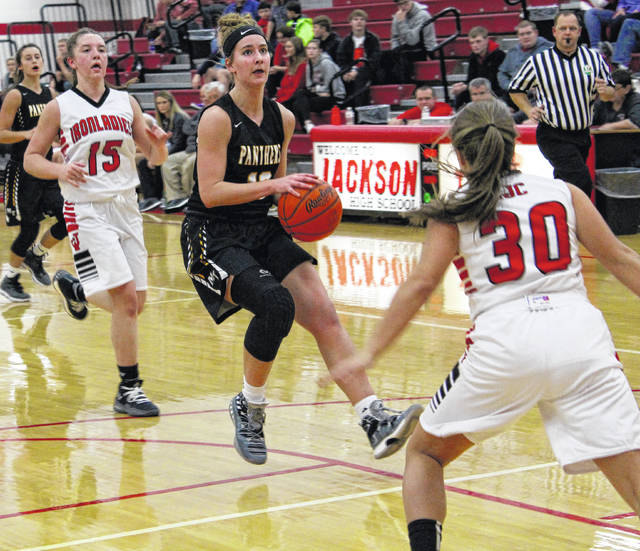 Miami Trace senior Victoria Fliehman (13) pulls up for a shot as Jackson's Raylene Hammond (30) and Raegan Hall (15) defend during Saturday's Frontier Athletic Conference girls basketball game at Jackson High School. Pictured in back, at left, is Miami Trace sophomore Shay McDonald.