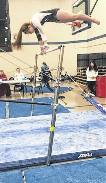 Devan Thomas does a horizontal cast over the uneven bars.