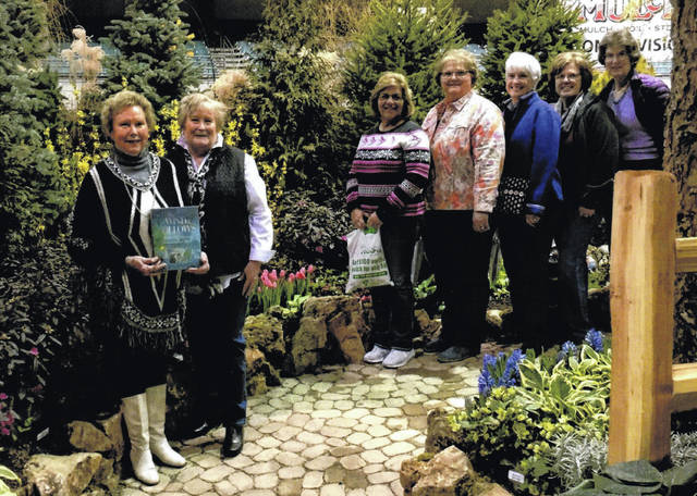 The Deer Creek Daisies visited 10 storybook gardens. They are shown walking down the path of The Wind and the Willow. Tulips, Hyacinths, Daffodils, Forsythia, Rhododendron were all in bloom. The group crossed a bridge overlooking swimming koi. Tall willow trees embraced the beautifully landscaped garden. From left to right: Connie Lindsey holding the storybook, Kendra Knecht, Shirley Pettit, Joyce Schlichter, Julie Schwartz, Jeanne Miller and Barbara Vance.