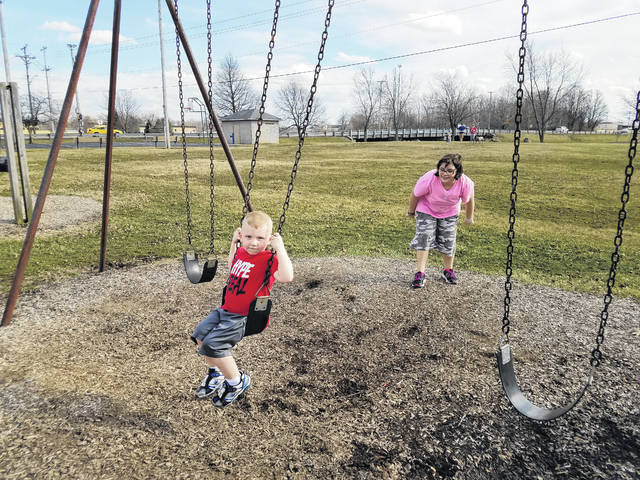 """With warm temperatures and sunshine Tuesday, Hunter and Halie Bryant, great-grandkids of Clarence Christman, spent the afternoon with their aunt """"Mi Mi"""" (Christman's granddaughter) learning about their great-grandfather and playing at the park dedicated to him."""