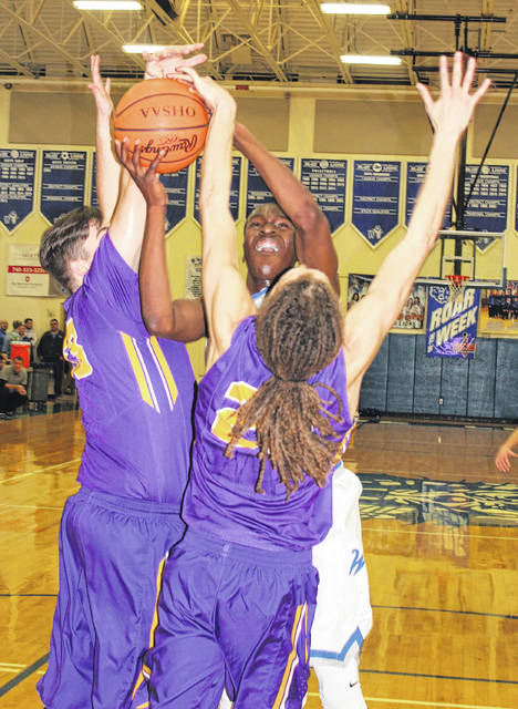 Washington junior Blaise Tayese puts up a shot against McClain's Landree Gray, right and Dakota Irvin during a Frontier Athletic Conference game Friday, Feb. 2, 2018 at Washington High School