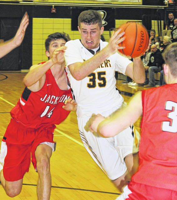 Miami Trace senior Darby Tyree cuts between two Jackson players in the final-ever boys game to be played at the Panther Pit Friday, Feb. 2, 2018. Tyree was the game's leading scorer with 21 points.