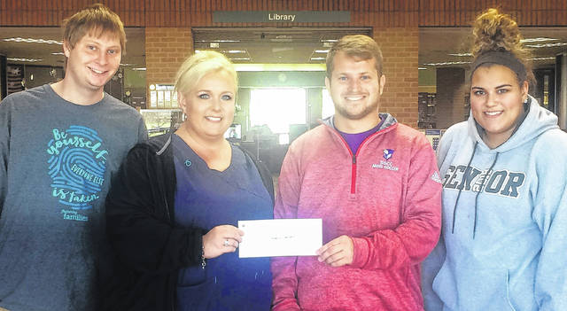 Members of Patriot Campus Ministries, a student group at Southern State Community College, make a donation supporting SSCC instructor Gregory Lawson (second from right) who traveled to Haiti to serve as an interpreter for deaf children. Pictured are Caleb Inlow, Angela Foreman, Lawson, and Jalyssa Carson.