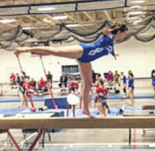 Jaina Applegate of Washington High School performs a scale to toe on balance beam.