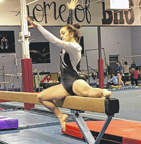 Maddie Southward mounts the balance beam to begin her routine.