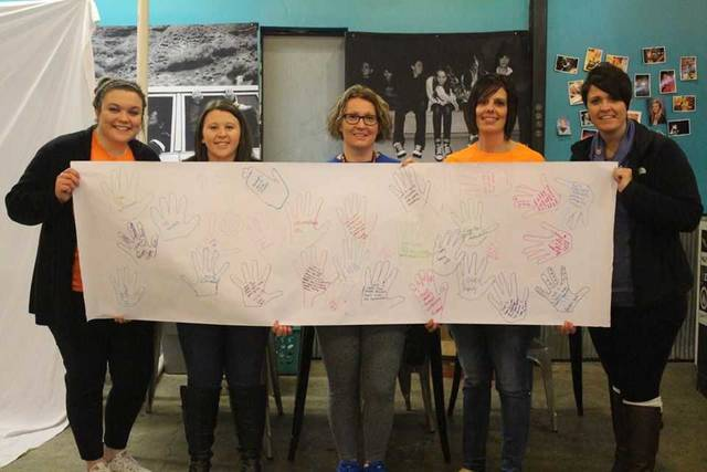 "The theme for this year's dance was ""Hands Unite."" During the dance the kids were asked to trace their hand and write ""what love is"" to them. When the project was complete the banner was given to Molly Gruber to be put on display at The Warehouse Youth Center."