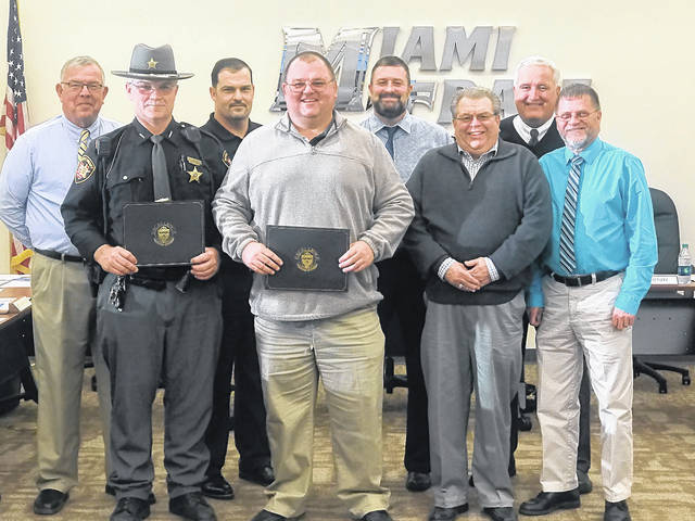 Fayette County Sheriff's Office Deputy Montana Coe, Miami Trace Resource and DARE Officer, and Jack Anders, Miami Trace Student Safety and Attendance Coordinator, were recognized during the Winner's Circle portion of the Miami Trace Local Schools Board of Education meeting Monday evening for their continued efforts to keep the kids and the campus safe. Pictured (L to R): front row: Deputy Coe, Jack Anders, Bruce Kirkpatrick and Dave Miller. Back row: Charlie Andrews, Rob Dawson, Dave Lewis and Mike Henry.