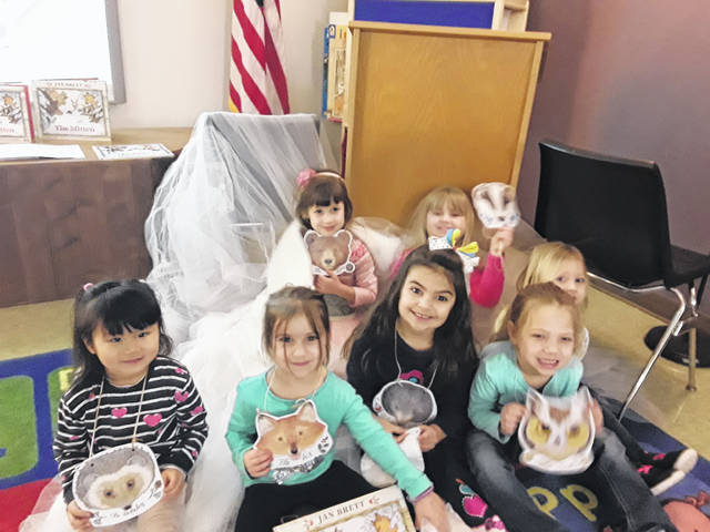 """At storytime this week, children acted out the play """"The Mitten"""" based on the classic book by Jan Brett. The actors each played an animal who wanted to stuff itself into a mitten to get out from the cold. Pictured (L-R) are Haniko, Felicity, Hartlyn, Macy, Adrianna, Ellie, and Abby."""