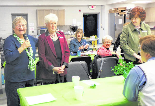 Sponsors of four potential new Altrusa members introduced their recommended candidates at the St. Patrick's meeting held recently at Fayette Progressive Industries. Kay Walker, chair of the Membership Committee, also spoke about several of the club's major service activities and had the members present name one additional place where each volunteers. Pictured are (from left) Elaine Crutcher presenting candidate Joyce Huntington, while members Janet Martin and Jeannie Bihl look on from the rear table; candidate Jennie Arnold (standing at the right) and member Lauran Perrill (back visible) also watch the introduction.