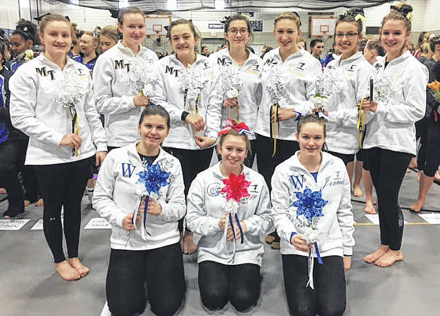 The Miami Trace gymnastics team prior to District meet processional; (front, l-r); Jaina Applegate (Washington High School), Lizzy Valentine (Greeneview High School) and Jenna Hinkley (Washington High School); (back, l-r); Devan Thomas, Debbie Abare, Maddie Southward, Grace Rolfe, Tori Waits, Gracie Greene and Abby Arledge.