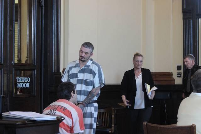 Public defense attorney Susan Wollscheid (standing center) emerges from a closed meeting with her client, Charles W. Pennington (standing left), minutes before a final plea and sentencing hearing was held with Fayette County Court of Common Pleas Judge Steven Beathard during open court Monday.