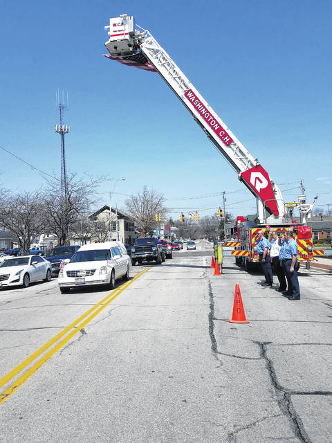 The funeral procession for Bill Crooks proceeded past the Washington Fire Department Friday under the ladder arches of the Washington C.H. and Jefferson Township fire departments.