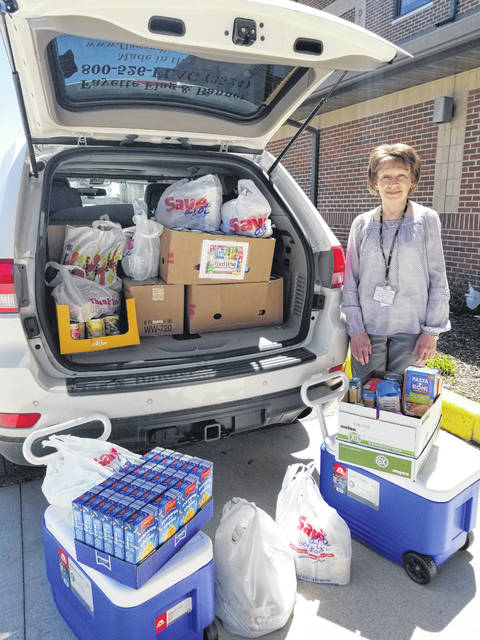 Cheryl Royster, social services director with the Fayette County Memorial Hospital, is pictured with food collected as part of the food drive.