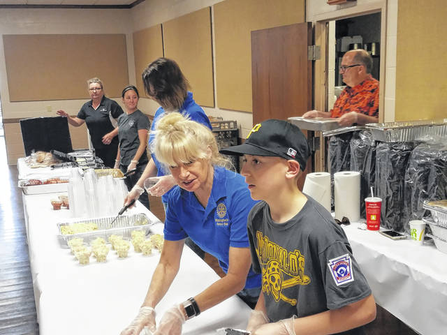 The Little League's 64th Anniversary Fish Fry, sponsored by the Washington Rotary Club, was held on Friday afternoon with many hungry residents coming out to enjoy a delicious meal. Community Action Commission of Fayette County Executive Director Bambi Baughn and McDonald's Little League team member Colten Brannigan volunteer in the take-out line during the event. Also pictured in the background are various volunteers assisting with the event.