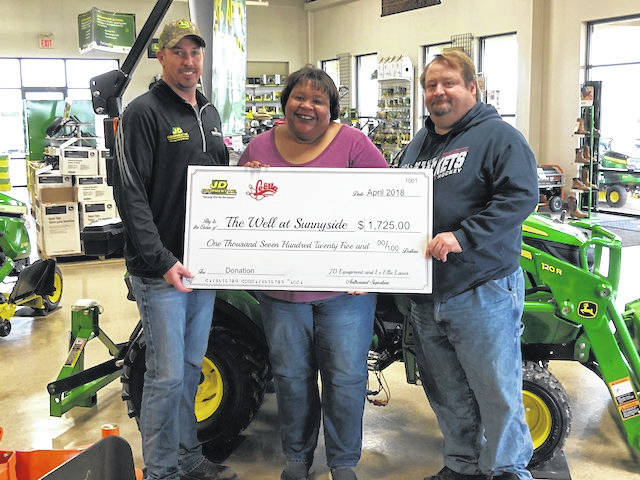 JD Equipment and LeElla Lanes recently partnered to raise money for The Well at Sunnyside. Pictured here is Chiquita Nash from the Well at Sunnyside receiving the check from Cody Kirkpatrick of JD Equipment and Ron Amore of LeElla Lanes.