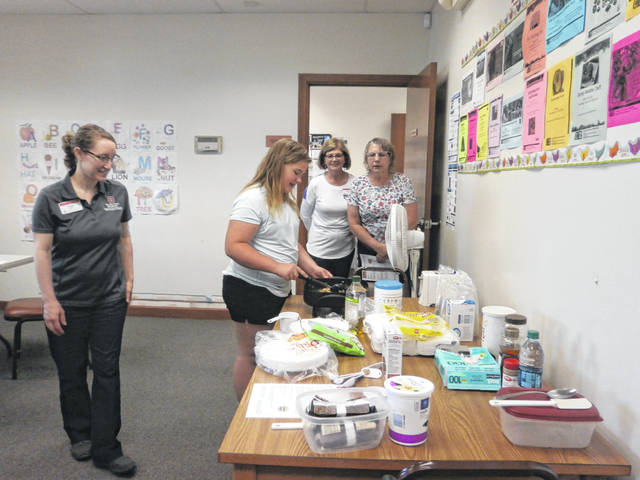 "Jeffersonville Branch Library hosted a nutritional program entitled ""Be A Rock Star With Breakfast."" Participants created delicious yogurt parfaits with fresh fruit and waffle sandwiches. Shown here are Fayette County Extension OSU Program Assistant: Sarah Sowell; Kylie, Monica Jones, OSU Extension, and Wendy."