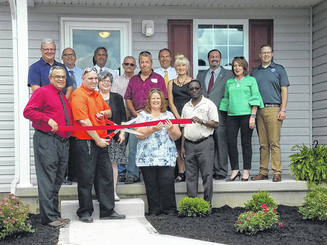 The Community Action Commission (CAC) of Fayette County helped celebrate the new home of Charles Cadamy on Wednesday afternoon on Staunton-Sugar Grove Road in Fayette County. Pictured (L to R): front row: Vernon Stanforth, Fayette County Sheriff; Charles Cadamy; Joy Stanforth; Joan Simmons, loan specialist with USDA Rural Development; and Godwin Apaliyah, director of Fayette County Economic Development. Back row: Dan Dean, Fayette County Commissioner; Joe Denen, Washington Court House City Manager; Steve Creed, CAC Self-Help Housing director; Jack DeWeese, Fayette County Commissioner; Tony Anderson, Fayette County Commissioner; Bob Peterson, State Senator (R-Washington Court House); Bambi Baughn, executive director of CAC; David Hall, USDA Rural Development State Director; Julie Bolender, president of the Fayette County Chamber of Commerce; and Trevor Patton, Washington Court House City Schools director of marketing and communications.