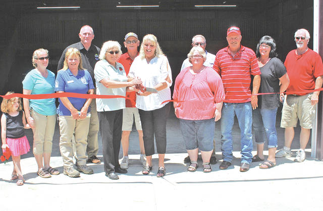 SATH Executive Director Linda Allen (on the right holding scissors) and Rocky Fork Regional Park Manager Tammy Knisley (on left holding scissors), with other dignitaries looking on, cut a ribbon marking the dedication of a new 64-foot by 48-foot storage building for KAMP Dovetail located at the Rocky Fork State Park Campground.