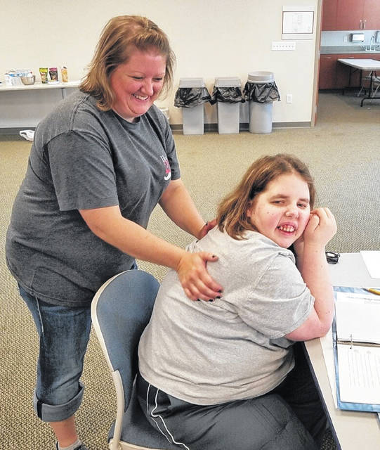 Stephanie Blair gives a neck and shoulder massage to class member, Chris. Massages help to relax and improve mood.