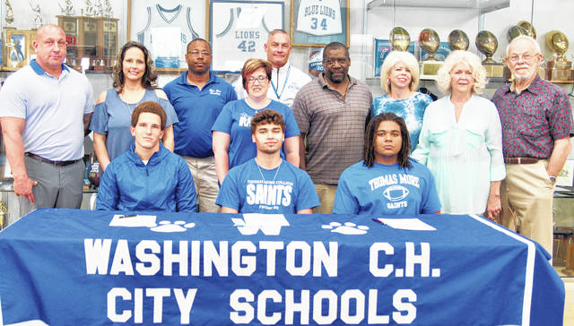 A trio of Washington High School members of the graduating Class of 2018, prior to their graduation signed letters of intent to attend Thomas More College, located in northern Kentucky. They will all play football for the Saints and Nelson will also be on the Thomas More wrestling team. They were joined for the special occasion by family and coaches. (seated, l-r); Caleb Rice, Zane Nelson and Derrick Wade; (back, l-r); Eric Rice, Jackie Kinney, Louis Reid, Heidi George, Chuck Williamson, Derrick Wade, Karen Wade, Patricia Whitmer and David Whitmer.