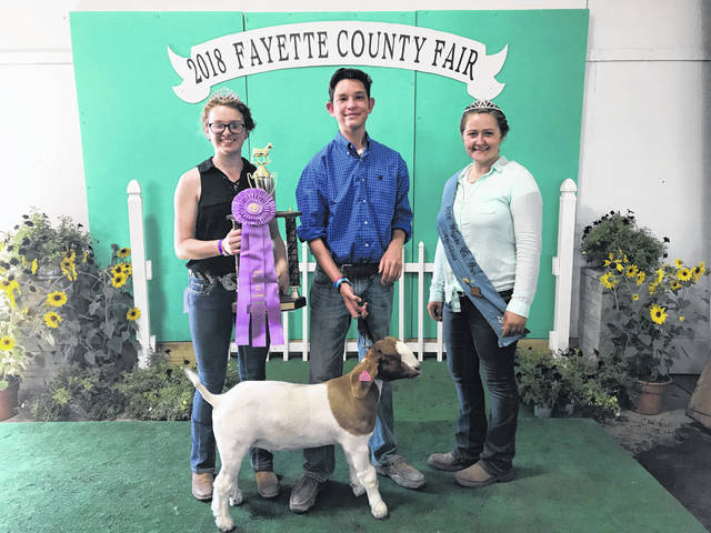 Drew Pontious won the reserve grand champion meat goat prize at Tuesday's Fayette County Junior Fair Boer Goat Show. Pontious is pictured with Cheyenne Williams (left), the meat goat ambassador, and Fayette County Fair Attendant Victoria Schappacher.