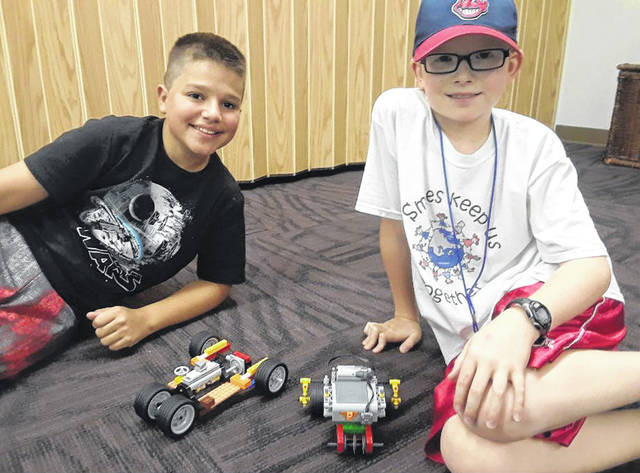 The Carnegie Public Library Children's department recently held a four-week class for third through sixth graders encouraging STEM education while building with Lego blocks. STEM is an acronym for Science, Technology, Engineering, and Mathematics, which are four subjects students need to master in the modern world. Charlie Reeves (on the left) built this car, which uses a crown gear to change the direction of his motor's axle. The car also has a simulated piston system. Isaiah Wynne (on the right) experimented with different gear ratios so his vehicle can be converted to either a fast moving car or a strong pushing bulldozer.