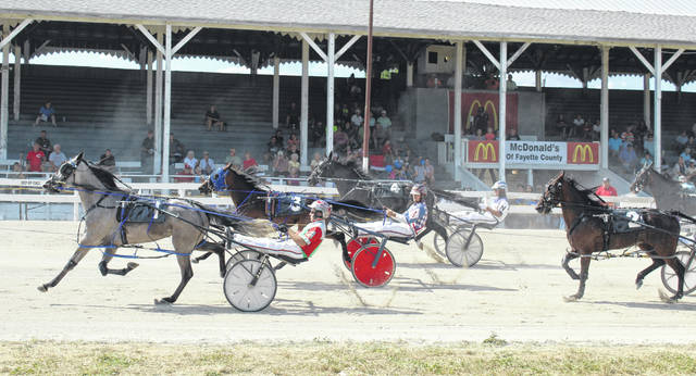 Horses travel past the grandstand during a race on Wednesday, July 18, 2018 at the Fayette County Fair. Another full card of racing is set for Saturday, beginning at noon and ending with the 14th race, the D.E. Mossbarger Fayette County Classic.