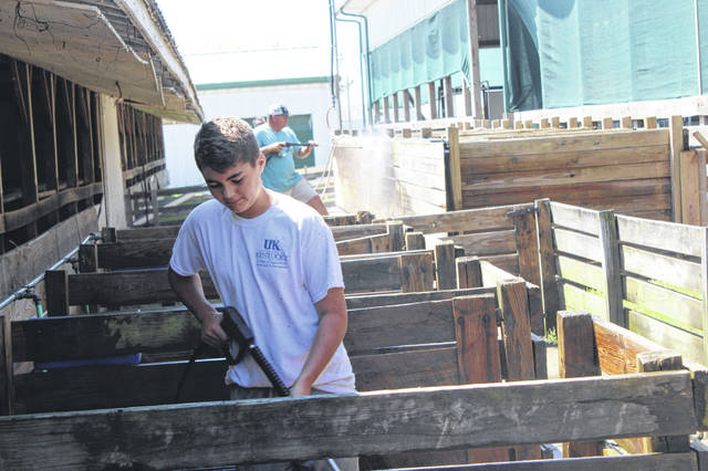 Preparation for the Fayette County Fair continued on Friday morning with volunteers and employees of all ages and from many different businesses visiting the Fayette County fairgrounds to help. Bryson Sheets helps clean swine stalls with a power washer with several other volunteers.