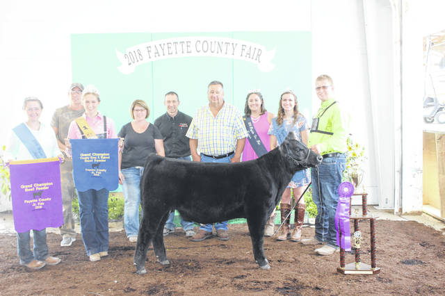 The Fayette County Junior Fair Beef Feeder Grand Champion — Quinton Waits — was named Tuesday afternoon following a three-hour show. Pictured with Waits (L to R): Fayette County Fair Queen Attendant Victoria Schappacher, Mike Rife, Fayette County Beef Queen Victoria Waits, Kris Waits, Daryl Waits, judge Oran Wolfe, Fayette County Fair Queen Jordan Bernard and Fayette County Fair Queen First Attendant Haley Copas. He also was named the Grand Champion Born and Raised Beef Feeder.
