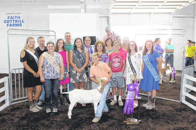 Corbin Melvin's grand champion boer goat sold for $2,250 at Thursday's Fayette County Boer Goat Sale. Corbin is the son of Don and Tabitha Melvin. Melvin is pictured with buyers and fair royalty, from left to right: (front row) Dog Ambassador Khenadi Grubb, Lamb & Wool Queen Abigail Mick, Fair Queen Jordan Bernard, Diane Munro of Faris Insurance, Weston Melvin (Corbin's brother), Meat Goat Ambassador Cheyenne Williams, Fair Attendant Victoria Schappacher, (back row) Daryl Waits of Fayette Veterinary, Judge Victor Pontious, Phil Grover of Maple Grove Farms, Carole Pontious of Maple Grove Farms, Tabby Melvin of Oakview Dermatology, and Don Melvin of Melvin Farms. Gustin Seed (Pioneer) was also part of the buyer's group.