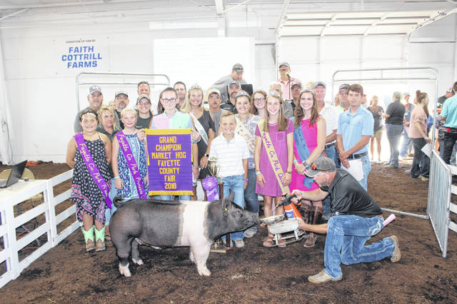 Zander Ivey's grand champion market hog sold for $3,400 at Thursday's Fayette County Market Hog Sale. Zander is the son of Amanda Ivey and Jim McCoy. Ivey is pictured with buyers and fair royalty, from left to right: (first row) Pork Princess Ella McCarty, Pork Princess Cotey Payton, friend Kaden Bryant, Pork Queen Aubrey McCoy, Fair First Attendant Haley Copas, (second row) Staci Payton of Family Farm & Home, Rebecca Heckathorn of Family Farm & Home, Fair Queen Jordan Bernard, Dog Ambassador Khenadi Grubb, Lamb & Wool Queen Abigail Mick, Meat Goat Ambassador Cheyenne Williams, (third row) Jon Wilt of Patchwork Gardens, Mark Sharp of Sharp Construction, Jim McDonald of McDonald & Son, Bryan Cockerill of Cockerill Farms, Kevin Gustin of Gustin Seed, (back row) Heath Bryant of Bryant Ag, Doug Shannon of Merchants Bank, Doug Coe of Gustin Seed, Rusty Coe of Coe Farms, Jason Langley of Langley Realty, and Jeff Wilt of Aluminum Works.