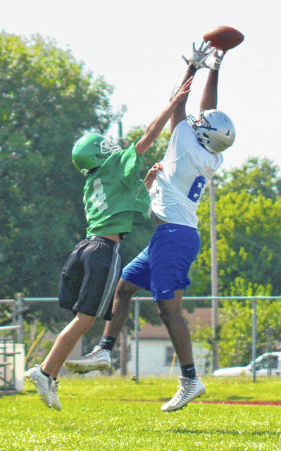 FOOTBALL IS IN THE AIR — The Washington Blue Lions held a 7-0n-7 passing scrimmage against the Huntsmen of Huntington High School Wednesday morning, July 12, 2018 at the WHS practice field. Above, senior Richie Burns (6) goes up to make a catch for the Blue Lions. Washington will have a scrimmage at Goshen Saturday, Aug. 11 at 10 a.m. There will be a jamboree at Amanda-Clearcreek Friday, Aug. 17 at 7 p.m. The Blue Lions open the 2018 season Friday, Aug. 24 at Blanchester. They will have their home-opener Friday, Aug. 31 at 7 p.m. against Circleville at Gardner Park.