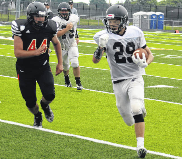Miami Trace junior Caden Sweitzer, at right, carries during a scrimmage against Waverly on the new field at Miami Trace Saturday, Aug. 11, 2018.