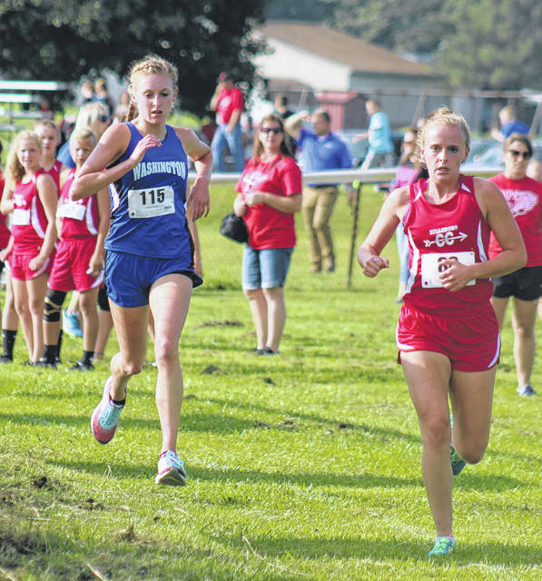 Washington's Cloe Copas (at left) runs in the McClain Invitational at Mitchell Park in Greenfield Wednesday, Aug. 22, 2018. She won the event in a time of 20:57.