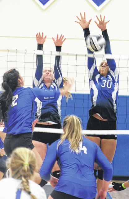 Washington senior Hannah Haithcock (30) goes up for the block, along with junior Halli Wall during the home-opener for the Lady Lions against the Southeastern Panthers of Ross County Thursday, Aug. 23, 2018.