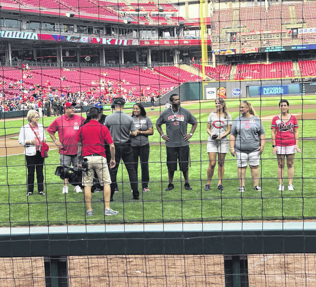 Greenfield resident Heather Gibson, second from right, is pictured on the field at Great American Ball Park before Tuesday's Cincinnati Reds game.