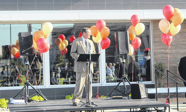 Dan Roberts, emcee of the grand opening event, spoke in front of a boisterous crowd Thursday morning.